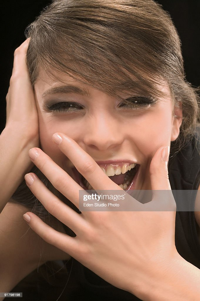 Woman laughing with hand covering mouth : Stock Photo