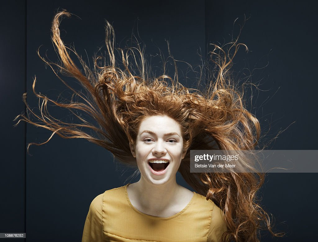 woman laughing with her hair blowing in wind.