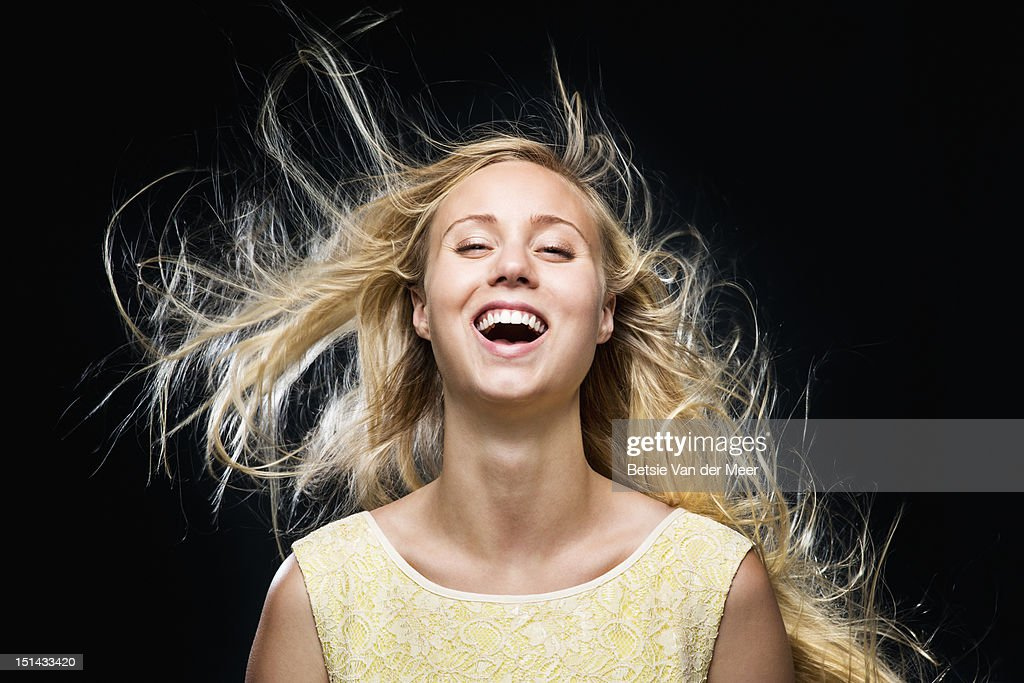 Woman laughing with wind blowing in hair.