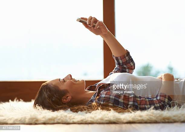 Woman laying down and using phone.