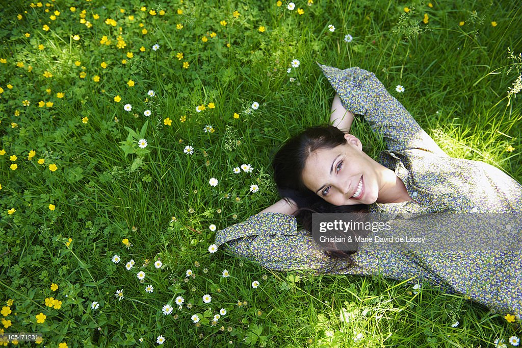 Woman laying down in the garden, smiling : Stock Photo