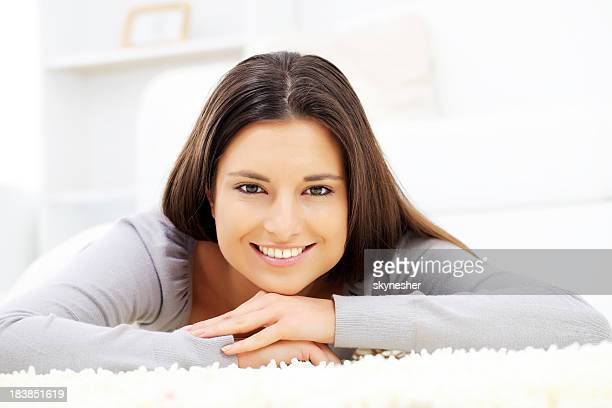 Woman laying down on the carpet and looking at camera.