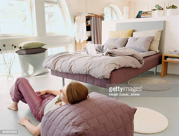 A woman laying down on the floor in a bedroom.