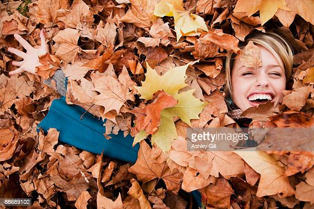 Woman laying in autumn leaves