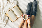woman laying in bed and read book with cup if coffee.woman laying in bed and read book with cup if coffee.woman laying in bed and read book with cup if coffee.