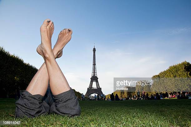 A woman laying in grass by Eiffel Tower, focus on feet