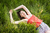 Woman laying in grass, smiling.