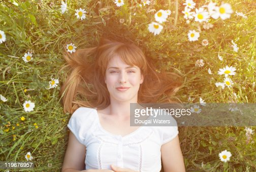 Woman laying in grass with daisies.