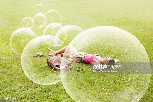 woman laying in grass, with floating bubbles