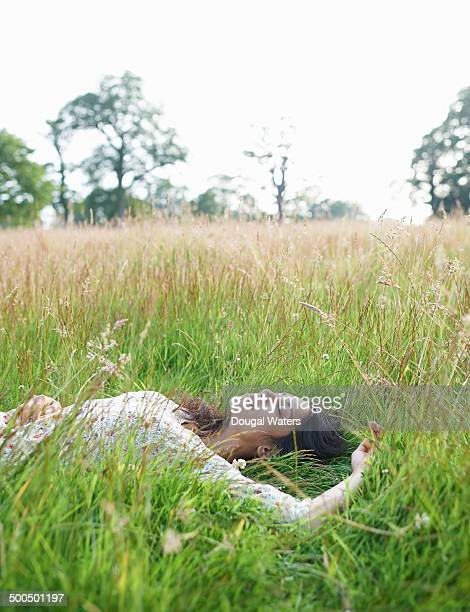 Woman laying in meadow with eyes closed
