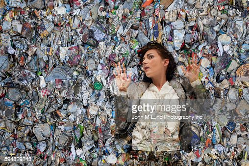 Woman laying in pile of compacted trash