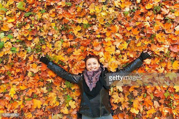 Woman  laying on autumn leaves.