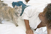 Woman laying on bed with cat