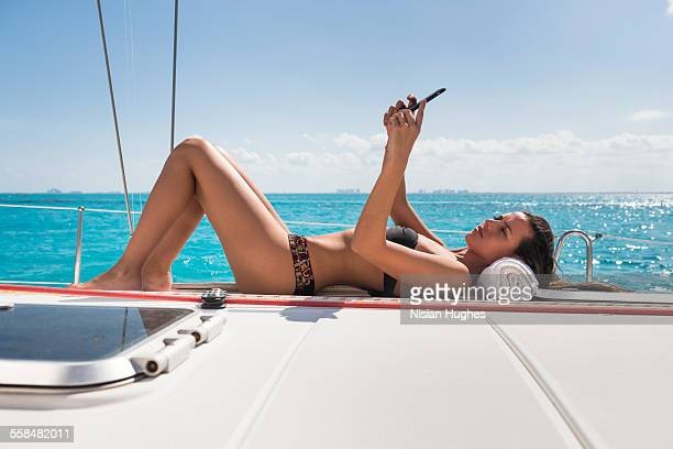 woman laying on deck of sailboat with cell phone