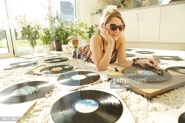 Woman laying on floor playing records