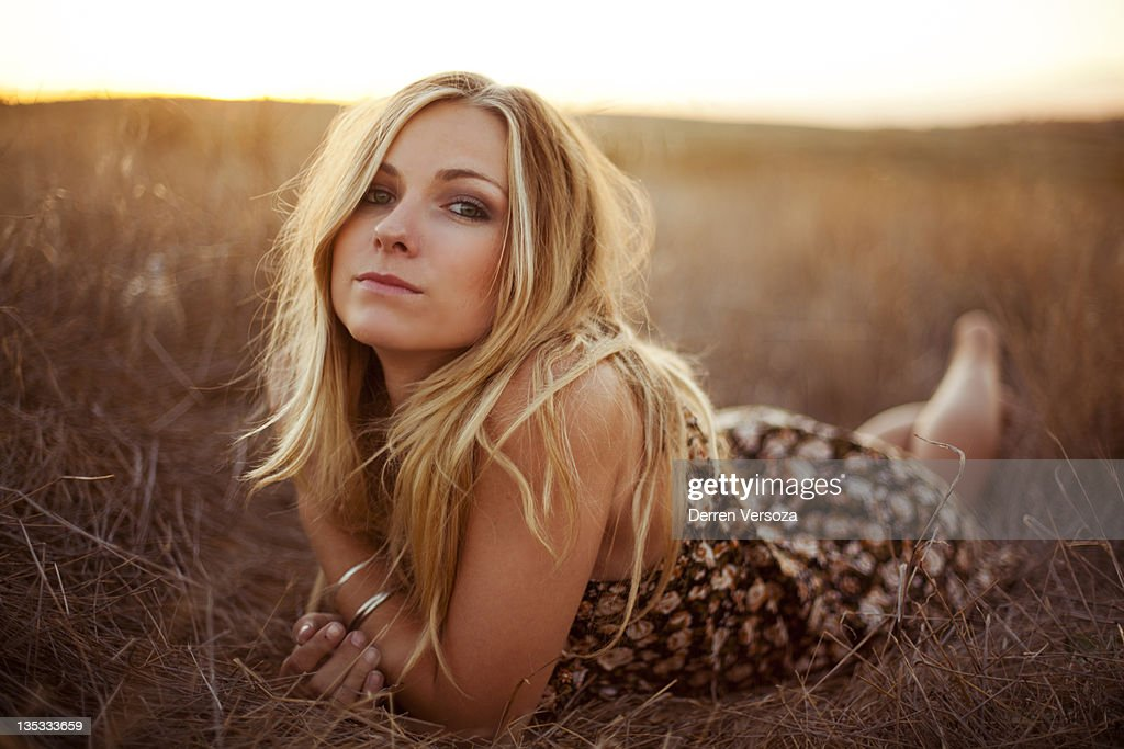 Woman laying on golden grass : Stock Photo