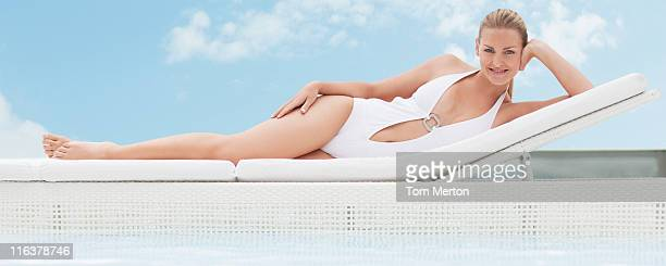 Woman laying on lounge chair at poolside