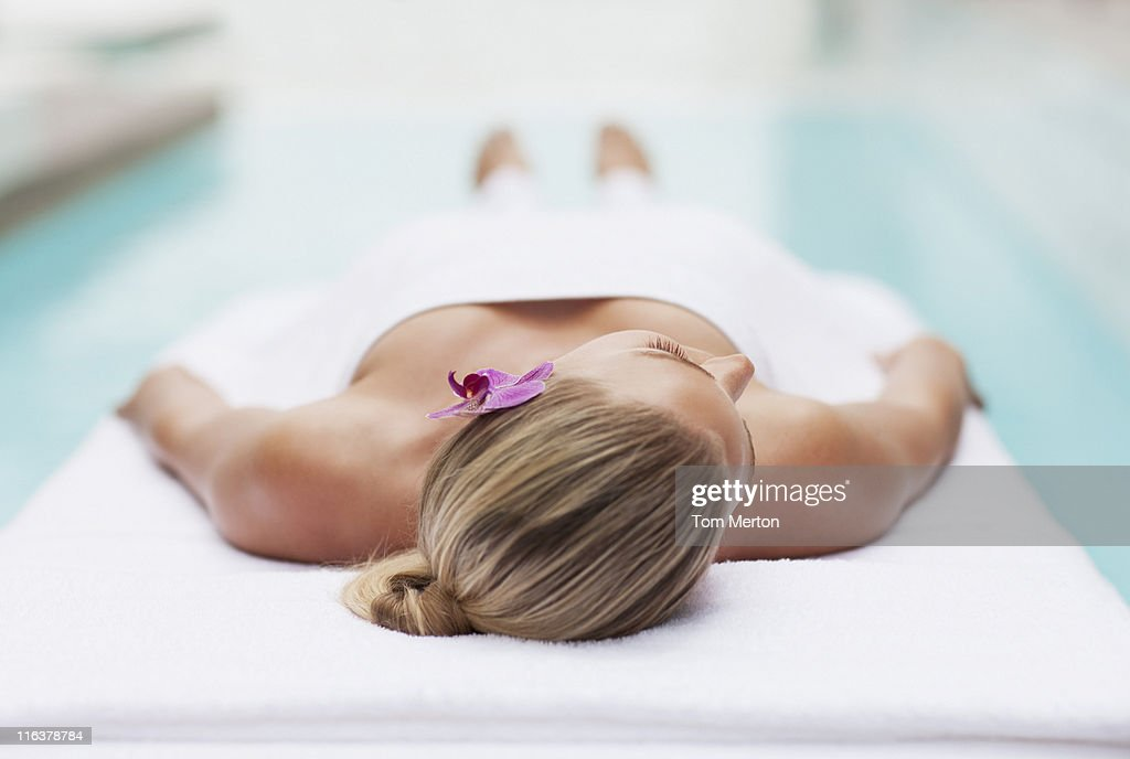 Woman laying on massage table at poolside : Stock Photo