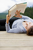 Woman laying on pier reading