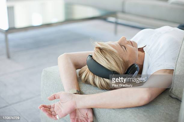 Woman laying on sofa listening to headphones