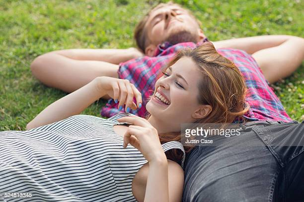 woman laying on the chest of a friend in the grass