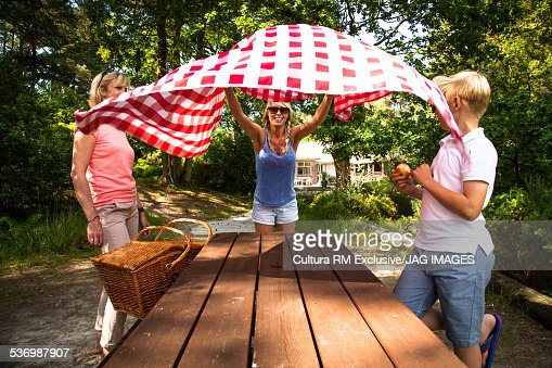 Woman laying table cloth for picnic in forest