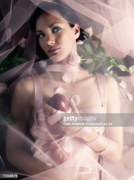 Woman laying under veil with apple and flowers