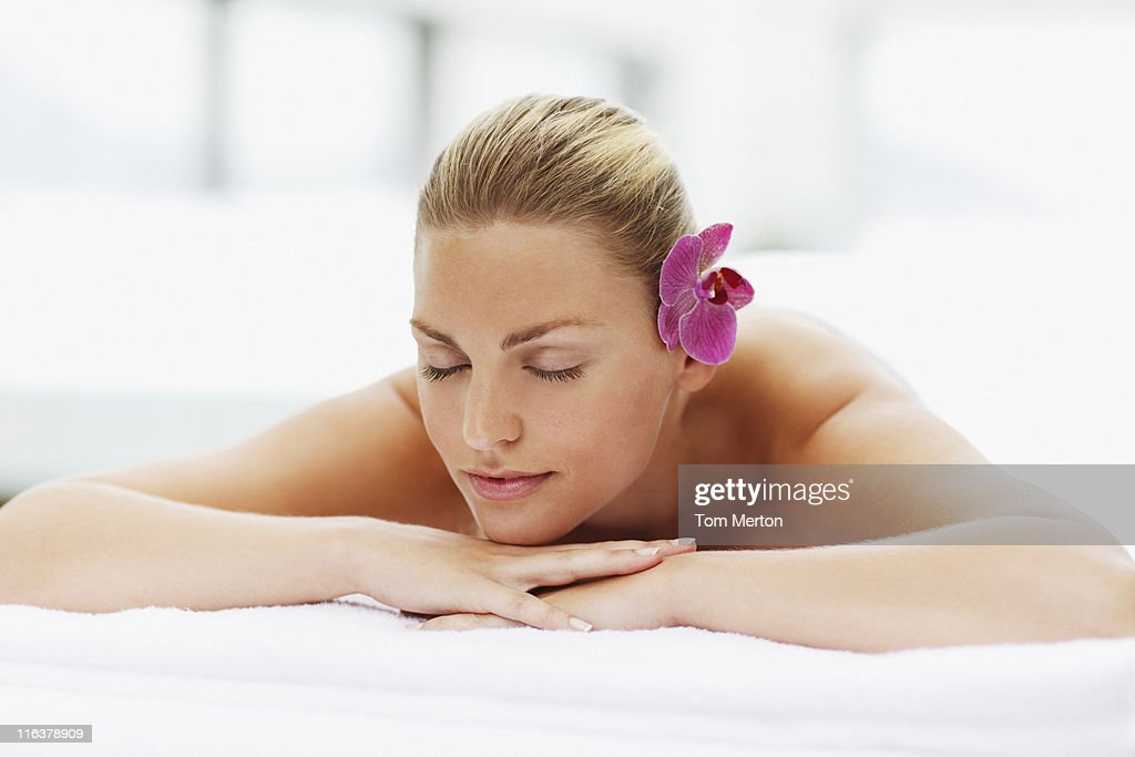 Woman laying with eyes closed on massage table : Stock Photo