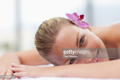 Woman laying with orchid in hair : Stock Photo