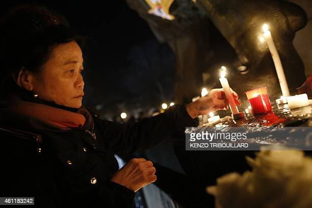 A woman lays a candle during a gathering on the Place de Republique in Paris on January 8 as a tribute to the 12 people killed by two gunmen at the...
