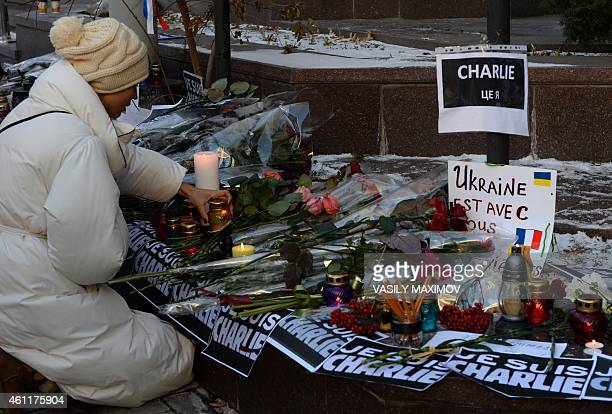 A woman lays a candle in front of the French embassy in Kiev on January 8 in tribute to the twelve people killed the day before in an attack by two...