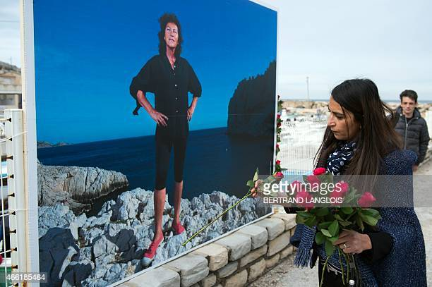 A woman lays a floral tribute during a ceremony to pay tribute to late French Champion sailor Florence Arthaud on March 14 2015 in Marseille southern...