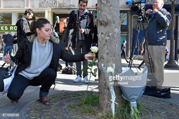 A woman lays a flower near the Marks and Spencer on the Champs Elysees in Paris following yesterday's shooting of a police officer on April 21 2017...