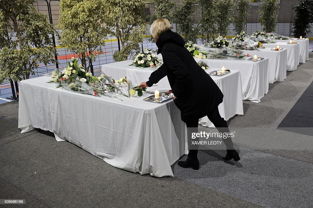 A woman lays candles and flowers on six tables representing coffins in Rochefort, on February 11, 2016, in tribute to the victims of the road accident between a school bus and a truck, killing at least six children. The head-on smash with a lorry carrying rubble came around 7:15 am (0615 GMT) in Rochefort in the western Charente-Maritime region. The school bus was carrying about 17 people, and three children suffered minor injuries in the accident, a police source said. / AFP / XAVIER LEOTY