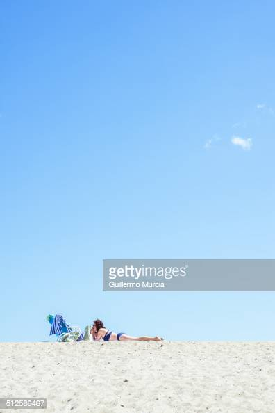 A woman lays down and gets a suntan atop the dunes at the Rockaway Beach in Queens New York August 24 2014