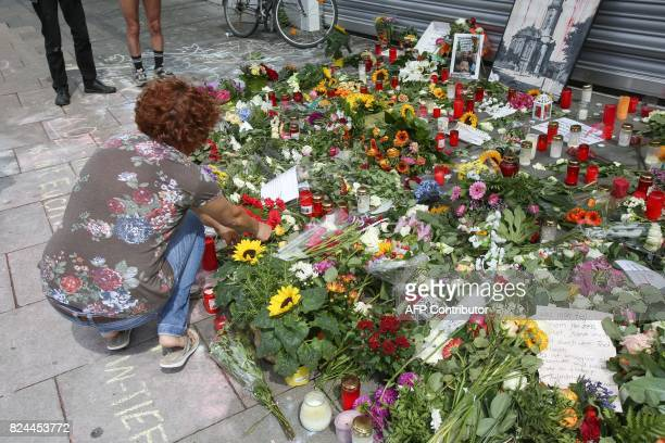 A woman lays down flowers at a makeshift memorial for the victims of a knife attack on July 30 2017 in front of a supermarket in Hamburg's Barmbek...