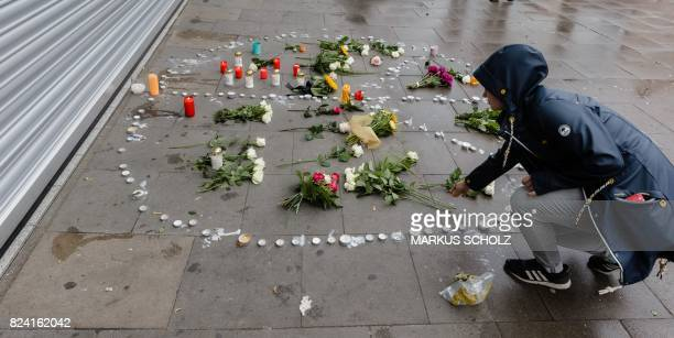 A woman lays down flowers at a makeshift memorial of flowers and candles arranged like a peace sign on July 29 2017 in Hamburg northern Germany at...