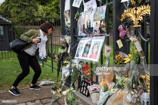 A woman lays floral tributes outside an entrance gate to Kensington Palace ahead of the 20th anniversary of the death of Diana Princess of Wales on...