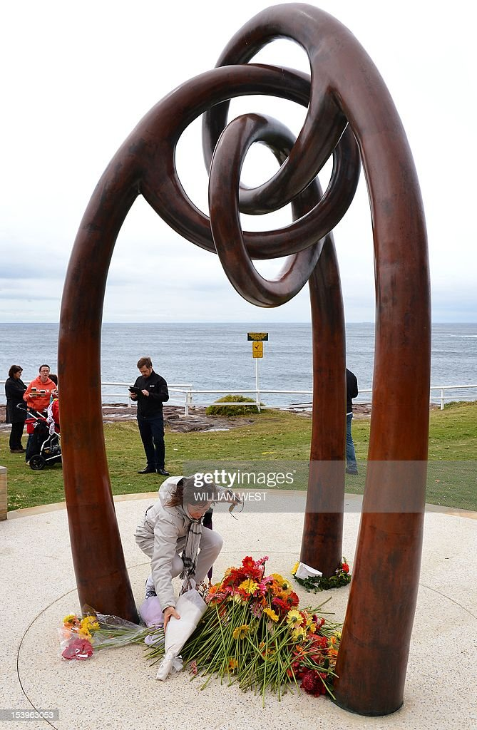A woman lays flowers after a ceremony to commemorate the 10th anniversary of the 2002 Bali attacks, at a memorial dedicated to Australians killed in the attacks, at Coogee Beach in Sydney on October 12, 2012. Survivors and relatives of the dead flocked to emotional Bali bombing ceremonies across Australia on October 12, with Foreign Minister Bob Carr praising the nation's mature response to the atrocity. AFP PHOTO/William WEST
