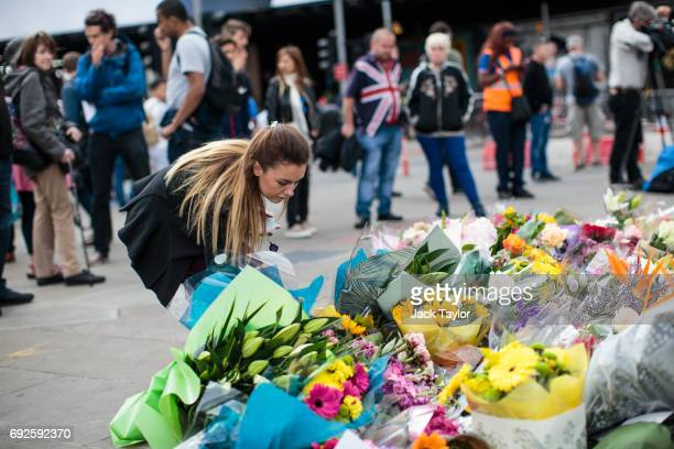 A woman lays flowers among other floral tributes left on London Bridge following the June 3rd terror attack on June 5 2017 in London England Seven...