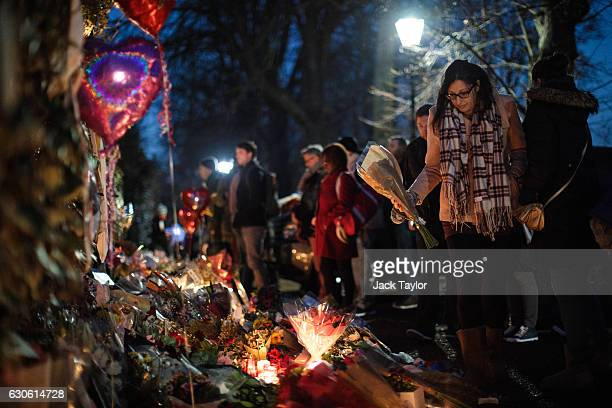A woman lays flowers among tributes outside the home of pop music icon George Michael in The Grove Highgate on December 28 2016 in London England...