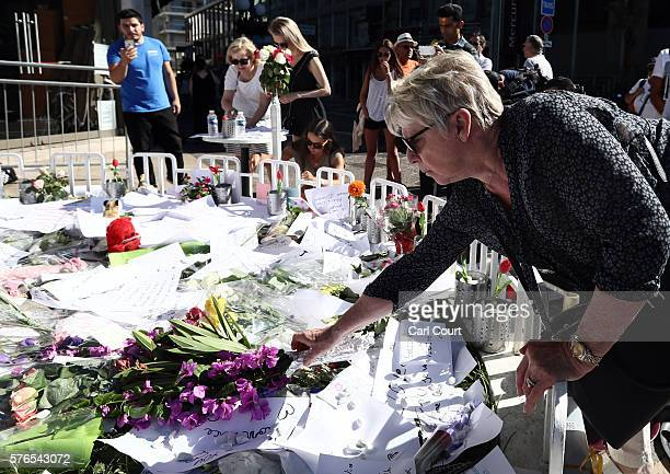 A woman lays flowers as people gather and lay tributes on the Promenade des Anglais on July 16 2016 in Nice France Five people believed to be linked...