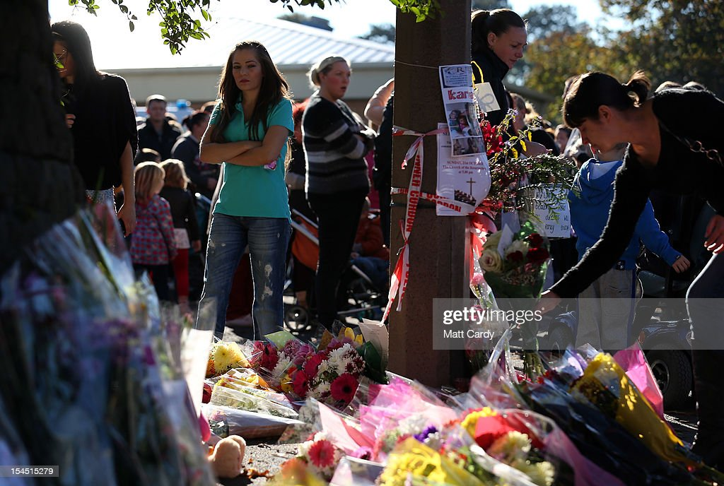 A woman lays flowers as she attends a local community memorial vigil outside Ely Fire Station for 32-year-old, Karina Menzies, who was killed in a hit-and-run collision on October 21, 2012 in Cardiff, Wales. Detectives are questioning a 31-year-old man arrested on suspicion of murder after a series of hit-and-runs in Cardiff that left a woman dead and 13 people injured. Nine casualties, five of them children, are still in hospital. Two adults are in critical but stable conditions.
