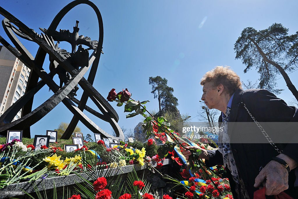 A woman lays flowers at Chernobyl's memorial during the commemoration ceremony at Chernobyl's memorial in Kiev on April 26, 2013. Ukrainians on Friday lit candles and laid flowers to remember the victims of the world's worst nuclear disaster at Chernobyl 27 years ago, as engineers pressed on with efforts to construct a new shelter to permanently secure the stricken reactor.