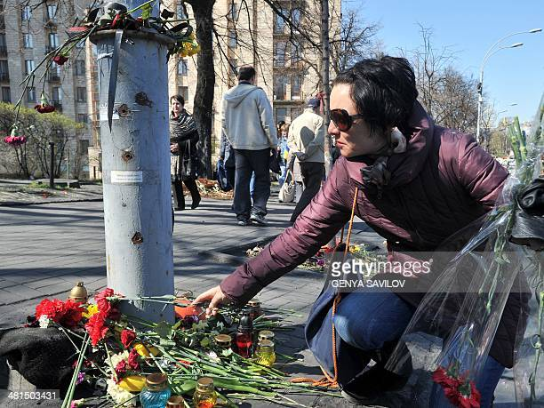 A woman lays flowers at the base of a lamppost marked with bullet holes which was turned into a makeshift memorial site for victims of recent clashes...