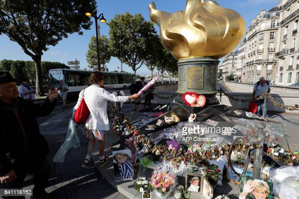 A woman lays flowers at the Flame of Liberty monument which became an unofficial memorial for Diana Princess of Wales who died in a car crash in a...