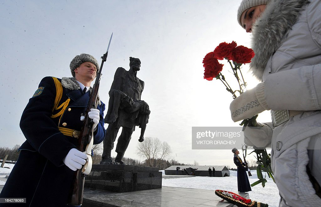 A woman lays flowers at the monument to the residents of the Belarus village of Khatyn burnt alive in 1943 by the Nazis with participation of Ukrainian and Belarusian collaborators, some 60 km northeast of Minsk, on March 22, 2013, during a ceremony to mark the 60th anniversary of the tragedy. Khatyn became a symbol of mass killings of the civilian population during the WW II fights between Soviet partisans, Nazi Germany's troops and their collaborators. AFP PHOTO / VIKTOR DRACHEV