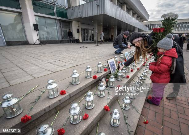 A woman lays flowers at the portraits of the NordOst musical hostage drama victims at the Dubrovka Theatre in Moscow on October 26 during a...