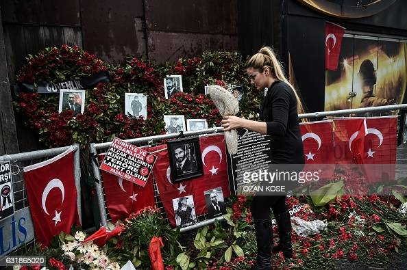 TOPSHOT A woman lays flowers by a makeshift memorial in front of the Reina nightclub in Istanbul on January 17 a day after Turkish police arrested...