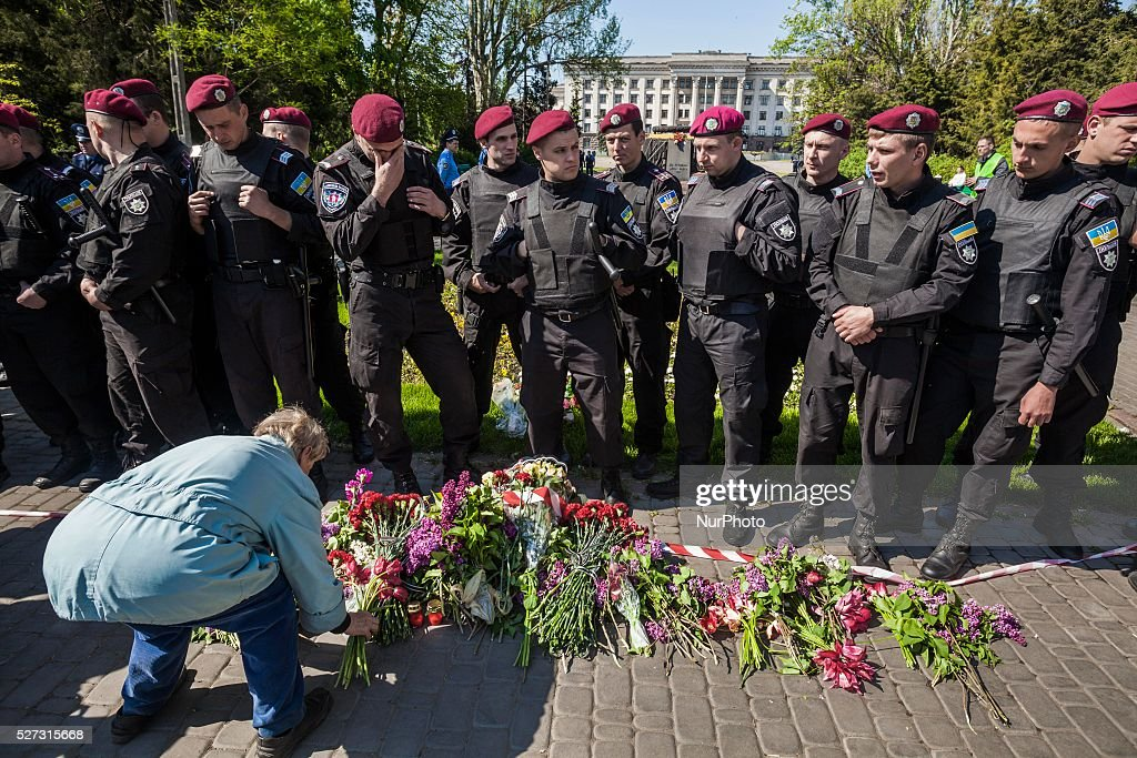 Woman lays flowers in front of the police riot in the entrance to Kulikovo Pole square in Odessa, southern Ukraine, on May 2, 2016 in remembrance of the deaths of 2nd of May clashes, on 2014. The square was closed because a bomb threat.